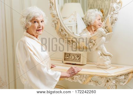 Joyful senior lady is standing near mirror in gorgeous robe. She is looking at camera and smiling