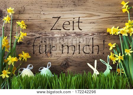Wooden Background With German Text Zeit Fuer Mich Means Time For Me. Easter Decoration Like Easter Eggs And Easter Bunny. Yellow Spring Flower Narcisssus With Gras. Card For Seasons Greetings