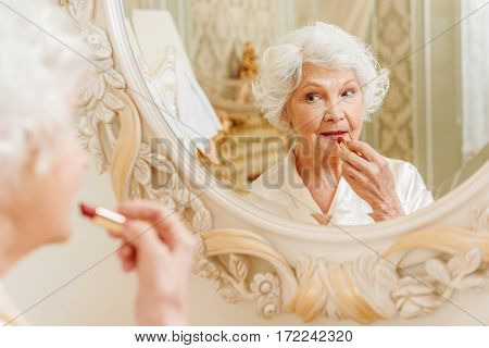 Senior woman is applying red lipstick on her lips. She is standing and looking at mirror with satisfaction
