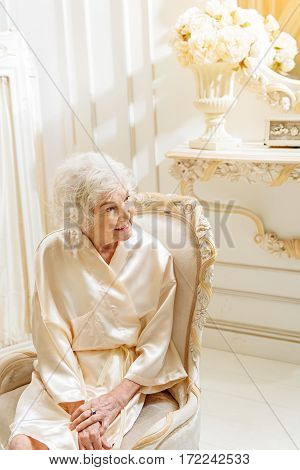 Cheerful senior rich lady is resting at her gorgeous apartment. She is sitting on chair and looking aside with happiness