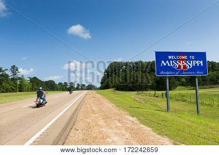 Two motorcycles passing by the Mississippi State welcome sign along the US Highway 61 in the USA; Concept for travel in America and Road Trip in America