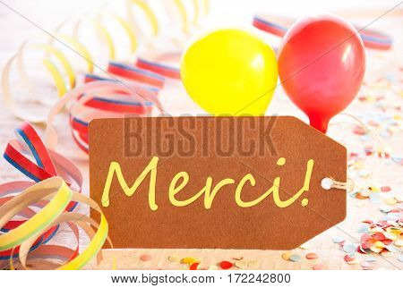 One Label With French Text Merci Means Thank You. Party Decoration Like Streamer, Confetti And Balloons. Wooden Background With Vintage, Retro Or Rustic Syle