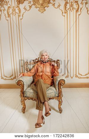 All world is beneath my legs. Elegant old woman is sitting on luxury armchair. She is smiling and looking at camera with confidence