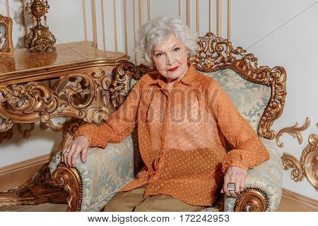 Severe old lady is sitting in her gorgeous apartment. She is looking at camera with seriousness