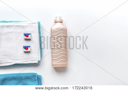 Bright clean towels pile with detergent and plastic conditioner bottles in laundry background top view mockup