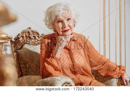 I am so lonely. Sad old lady is sitting on comfortable chair and looking at camera pensively