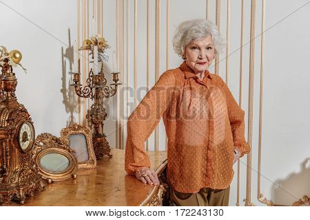 That is my luxury house. Confident old woman is standing and leaning hand on table with expensive decorative things