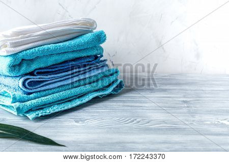 blue towels pile in housekeeping set on laudry gray background mock-up