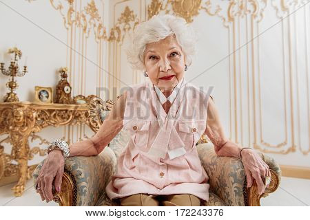 Look into my honest eyes. Sly old rich woman is sitting on luxury chair and staring at camera with innocence
