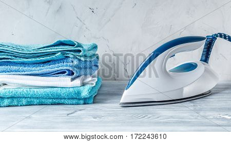 housekeeping set with towels and iron in laundry on gray desk background