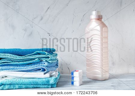 Pile of colorful clean towels with detergent on laundry gray background mock up