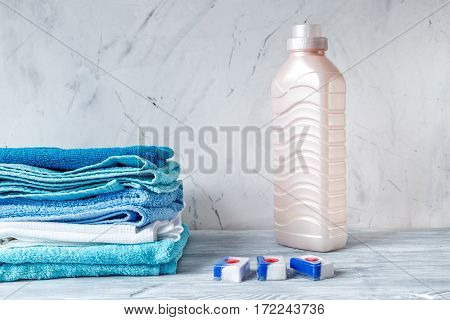 housekeeping set with towels and plastic bottles in laundry on gray desk background mock-up