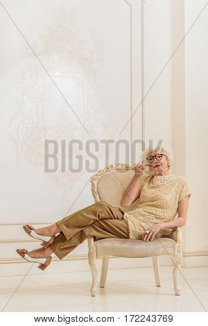 Relaxed old woman with eyeglasses is sitting on confortable armchair. She is smoking cigarette with pleasure