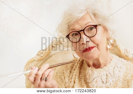 Elegant mature lady is holding tobacco pipe. She is sitting on chair and looking at camera with seriousness