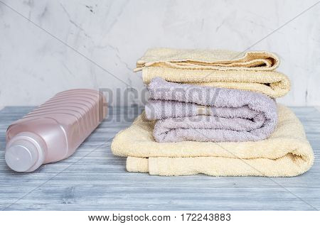 laundry set with bright towels and plastic bottels of detergent on gray table background