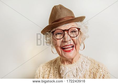 Happy old woman is standing and laughing. She is wearing eyeglasses and hat. Isolated and copy space in left side