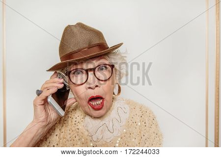 Senior lady is crazy about modern technology. She is talking on smartphone. Granny is standing with open mouth and looking forward with surprise