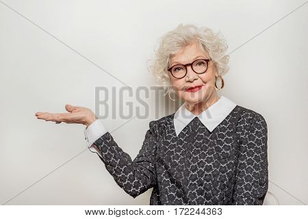 Elegant old woman is presenting something and smiling. She is standing and raising hands sideways. Isolated