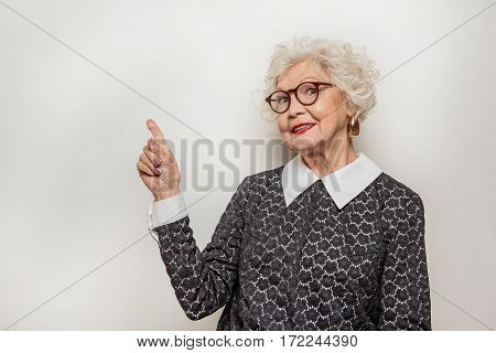 Look at this. Friendly senior lady is pointing finger up and smiling. She is standing and looking at camera with joy. Isolated and copy space in left side