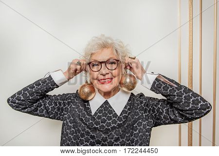 I am ready for celebration. Joyful mature woman is holding golden decoration Christmas balls near ears. She is standing and smiling