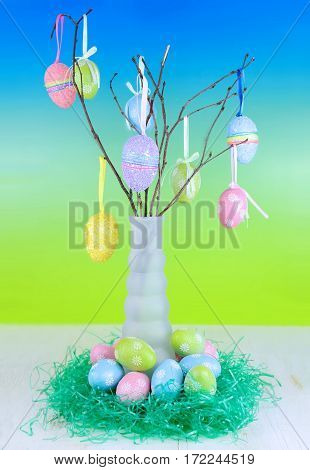 An Easter Tree of sparkly colorful eggs hanging from small tree branches in a tall vase. More eggs around the base in green Easter grass. Wood table with green and blue background