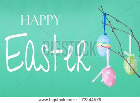 An Easter Tree of sparkly colorful eggs hanging from small tree branches in a tall vase. More eggs around the base in green Easter grass. Wood table with green background