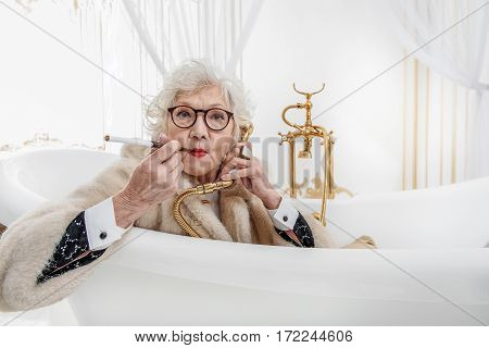 Wealthy senior lady is sitting in bath and smoking cigarette. She is holding faucet near ear as telephone. Lady is looking at camera with seriousness