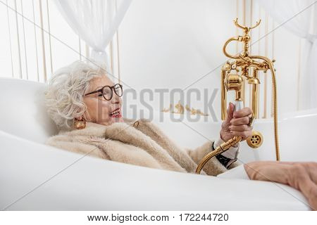 It is time to wash my body. Joyful old woman is holding shower tap under her fur coat. She is lying in bath and laughing