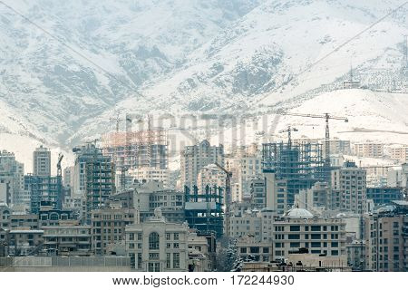 New high buildings beside snowy mountains are at construction stage