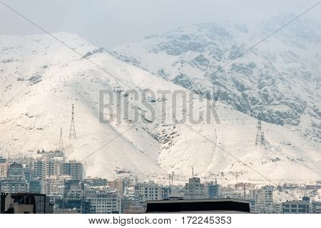 Town with modern high-rise is close to picturesque hills covered with snow