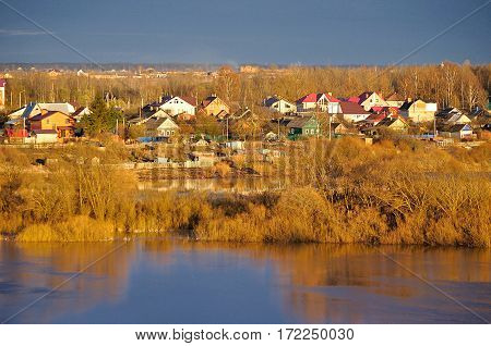 Spring landscape - countryside at sunset, birds eye view. Russian nature landscape view of small village from height - Russian countryside in the early spring time, aerial view of Russian village near the river.