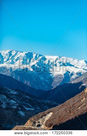 Great hills with snow caps are rising up to clear blue sky. Sun lit tunnel