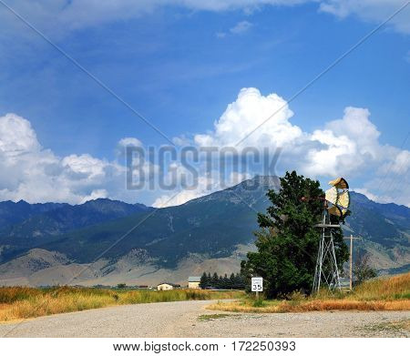 Crossroad is marked by a 35 mph speed limit sign. Windmill sits at corner of where these two narrow gravel roads meet. Absaroka Mountains stand in background.