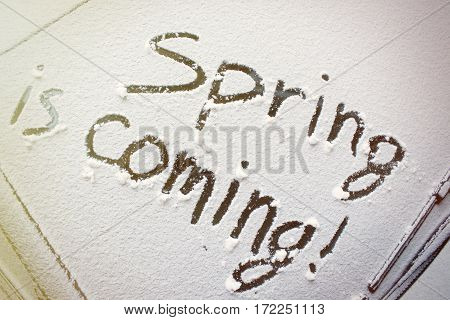 the inscription on the snow-covered car windshield spring is coming.