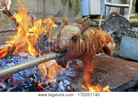 Suckling pig on a rotating spit with fire and sparks around