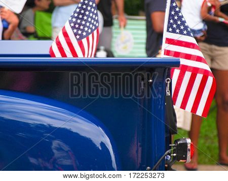 American flags attached to a bright blue classic truck driving in a Fourth of July parade. poster