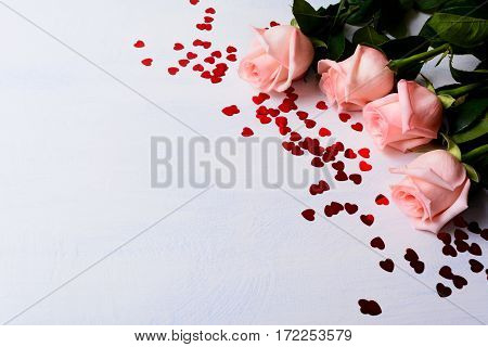 Wedding background with pale pink rose and red hearts. Elegant St. Valentine greeting card with flower and holiday symbol. Copy space.
