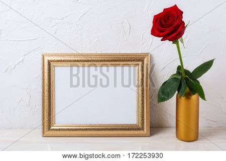 Landscape gold frame mockup with red rose in vase. Empty white frame mock up for presentation design.
