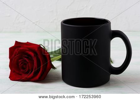 Black coffee mug mockup with red rose. Empty mug mock up for brand promotion.