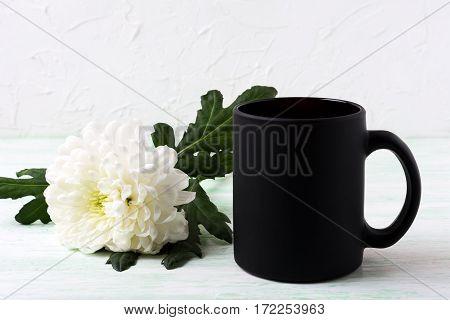 Black coffee mug mockup with white chrysanthemum. Empty mug mock up for brand promotion.