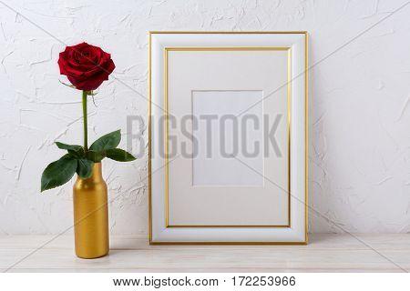 Frame mockup with burgundy red rose in golden vase. Empty gold decorated frame mock up for presentation artwork.