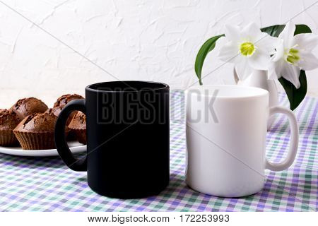 White and black mug mockup with chocolate muffins. Empty mug mock up for design presentation.