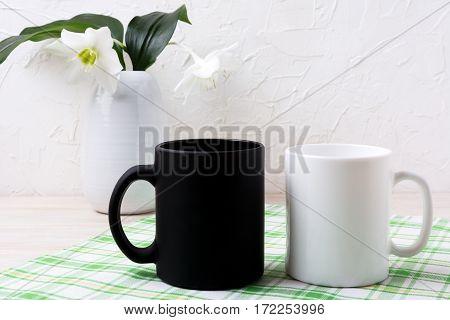 White and black mug mockup with lily in vase. Empty mug mock up for design promotion.