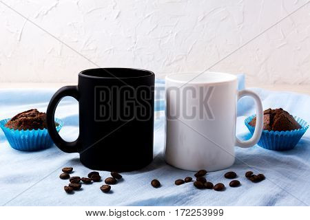 White and black mug mockup with coffee beans and muffins. Empty mug mock up for design presentation.