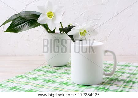 White mug mockup with lily in vase on green checkered napkin. Empty mug mock up for design promotion.