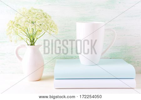 White cappuccino mug mockup with wild meadow flowers in pitcher. Empty mug mock up for design presentation.