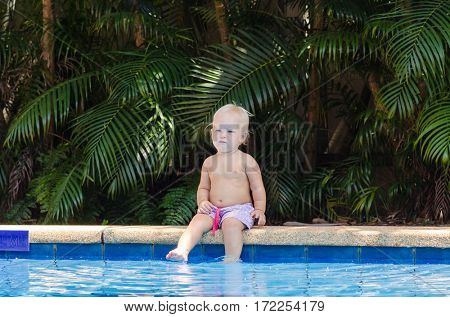 The child sits on the edge of the pool. Little baby is resting near the pool.