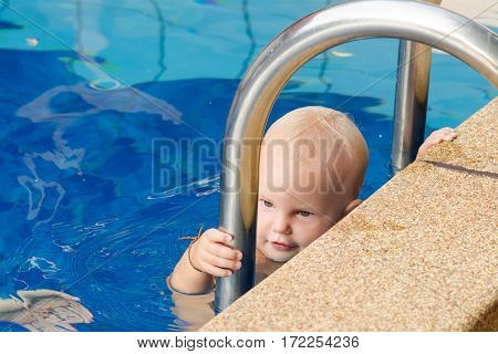 Small child tries to climb out of the pool. The girl holds hands for a side and handrails.