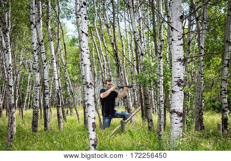 horizontal image of a young caucasian man out in the woods shooting his rifle on a warm summer afternoon.