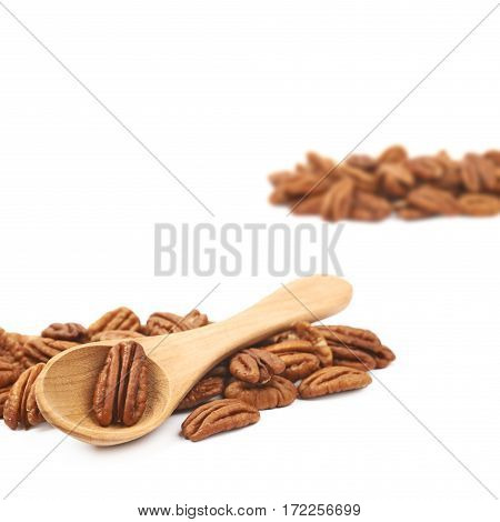 Pile of pecan nuts with the wooden spoon over it, close-up crop composition isolated over the white background